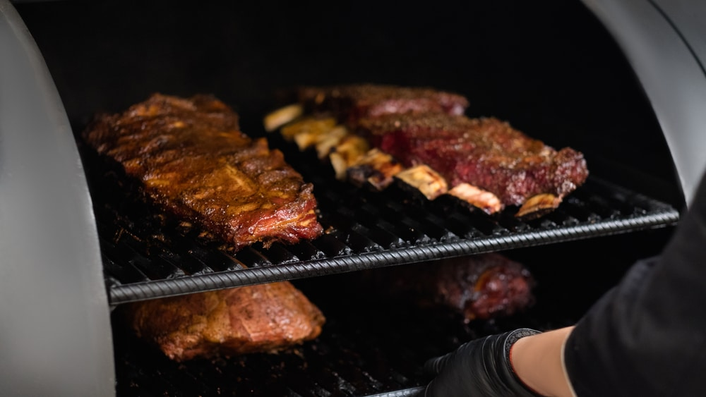 A barrel grill is used to prepare a large amount of meat