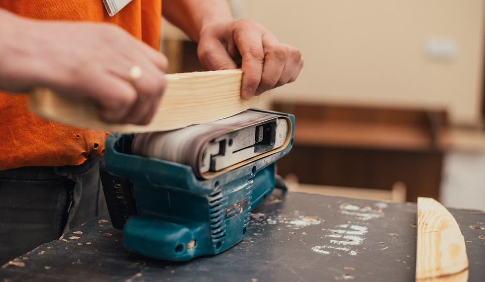 A carpenter sanding a wood using a benchtop equipment in a workshop