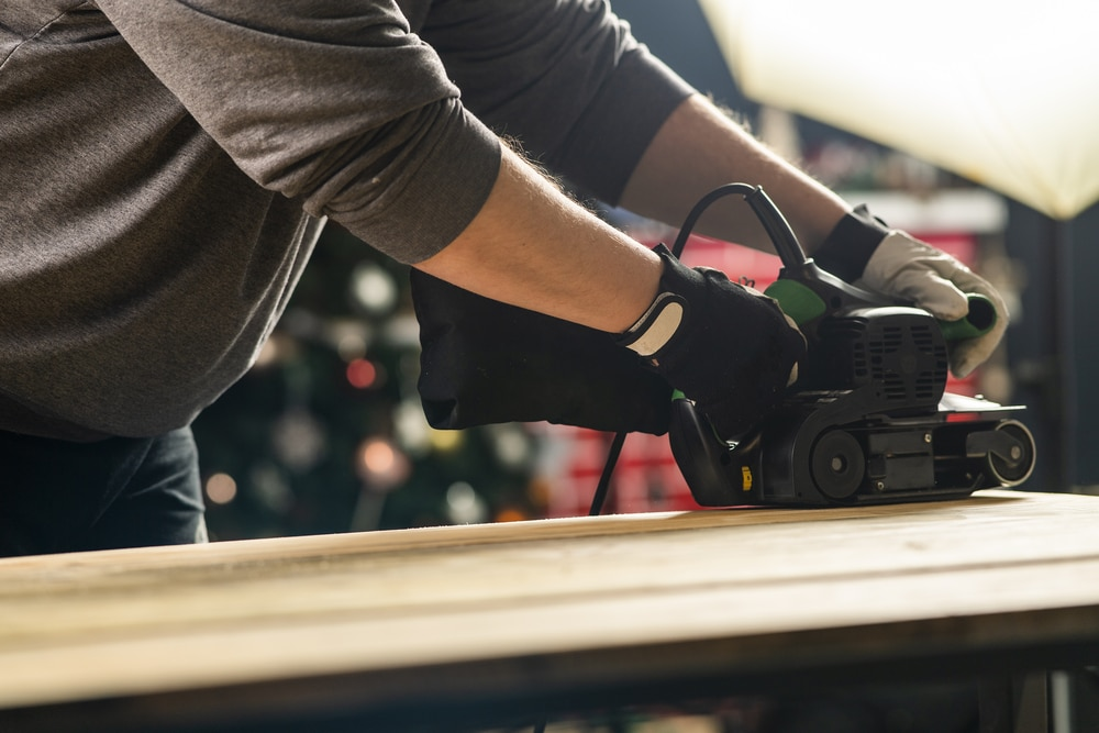 A man sanding a piece of wood using an electric tool.