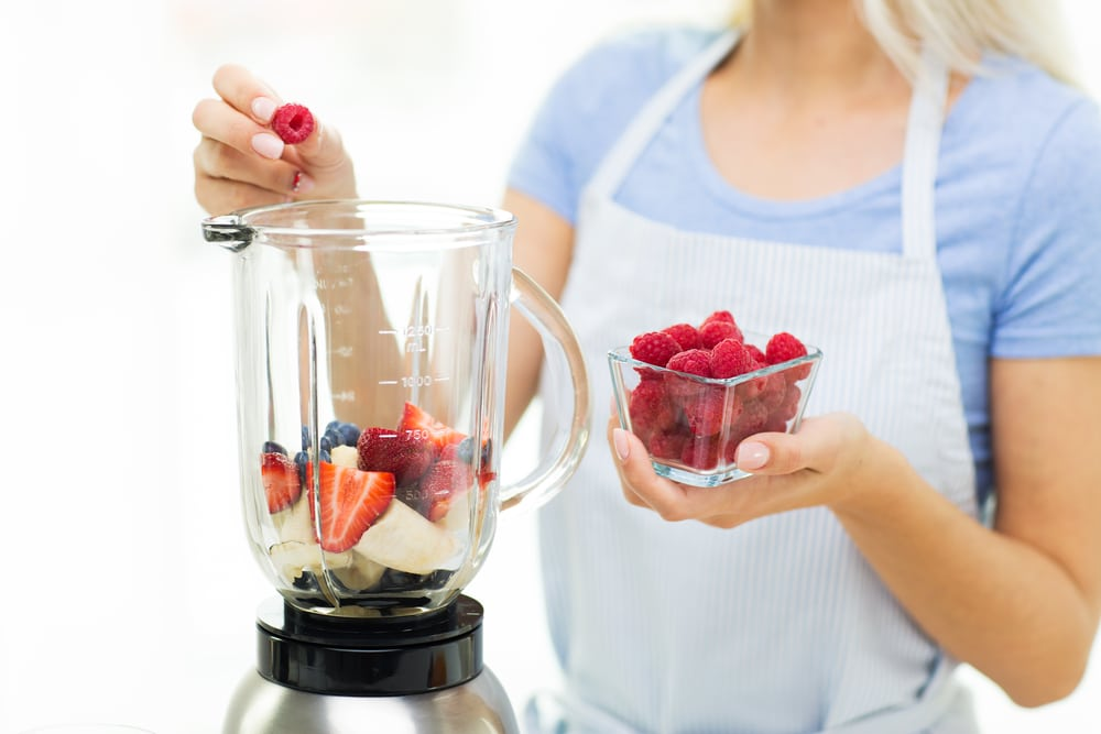 a woman making a healthy strawberry smoothie